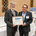 Ernesto Vargas of JP Cleaners accepts the Small Business Champion Award from Michael Ellenbecker of TURI