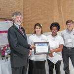 Mike Ellenbecker, TURI presenting award to Geneva Garcia, Jahara Bradshaw, and Andre Chandonnet from YWCA of Lowell